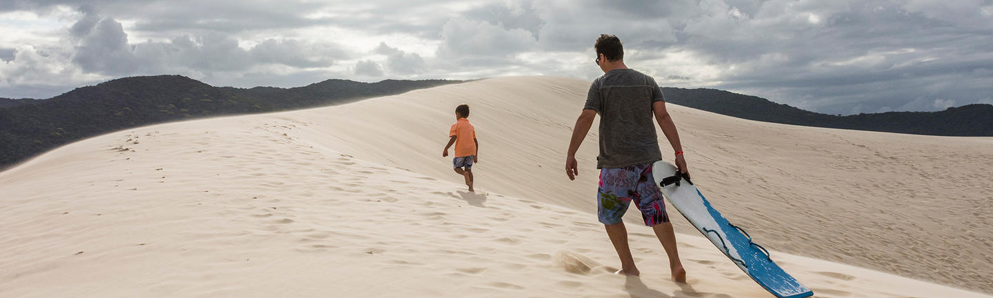 Travel insurance sandboarding, father and son, Brazil